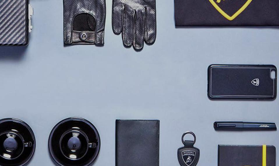 Immagine che mostra un piano con diversi accessori Lamborghini, tra cui guanti in pelle e cover per cellulare.