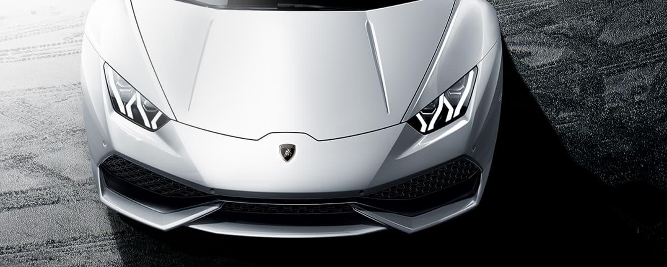 Das Bild ist eine Großaufnahme der Draufsicht eines weißen Lamborghini Huracán Coupé, von dem Haube und Scheinwerfer sichtbar sind.
