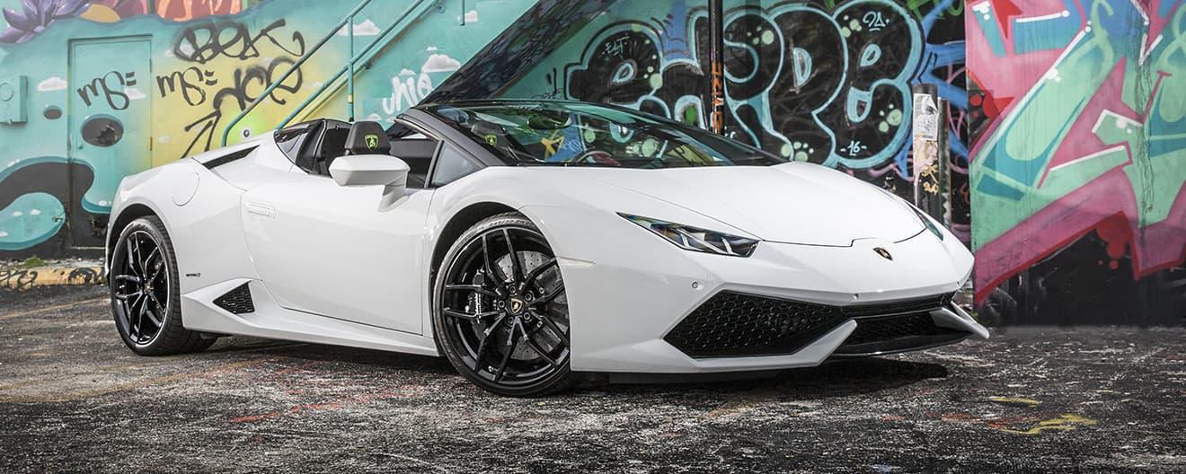 Bild, das den vorderen Teil eines weißen Lamborghini Huracán Spyder in Dreiviertelansicht zeigt, der vor einem Graffiti steht.