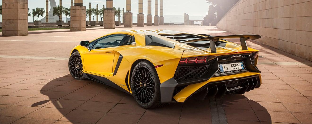 Image de l'arrière d'une Lamborghini Aventador SV Coupé jaune vue de trois quarts sur une terrasse panoramique.